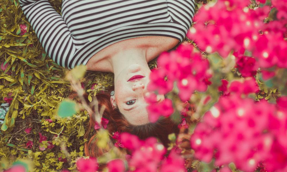жінка лежить під квітучим кущем