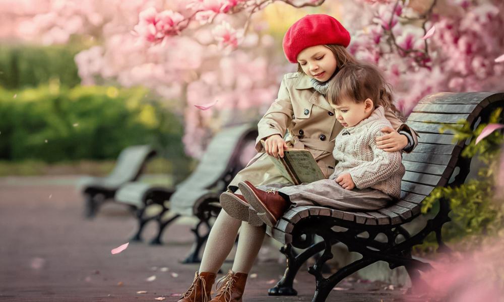 дівчинка і хлопчик на лавці читают книгу