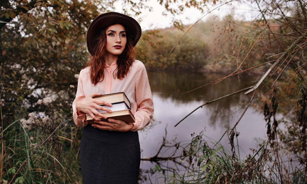 дівчина біля озера з книгами