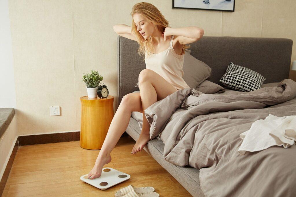жінка прокидається і стає на вагу