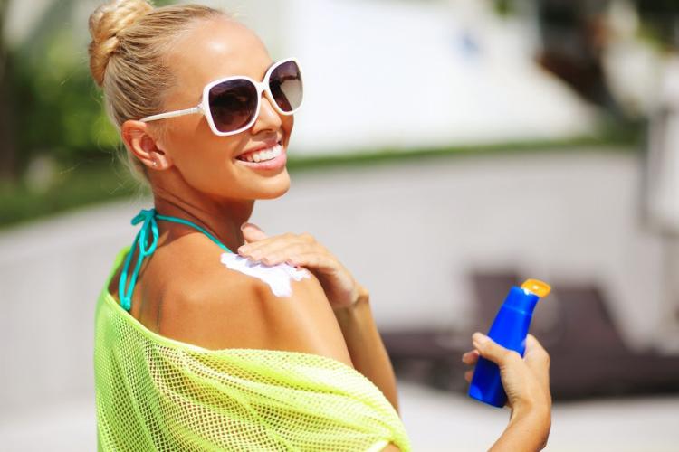 дівчина в сонцезахисних окулярах наносить на плечі сонцезахисний крем