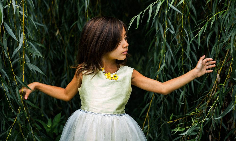 дівчинка стоїть біля верби