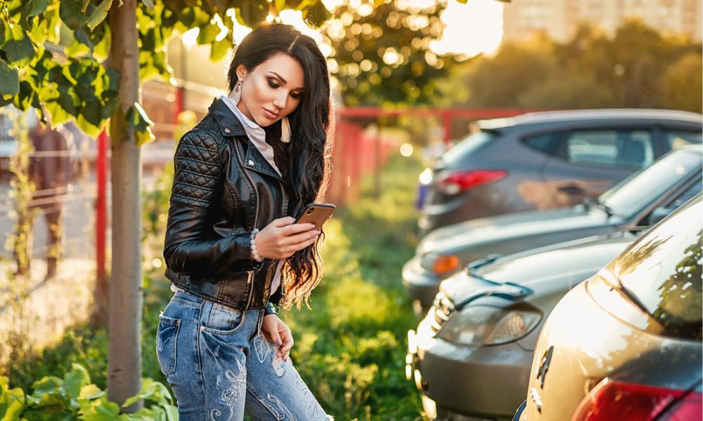 дівчина на вулиці дивиться у смартфон