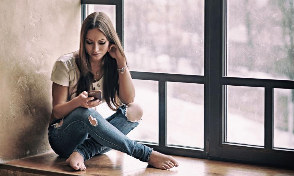 дівчина з телефоном сидить на вікні