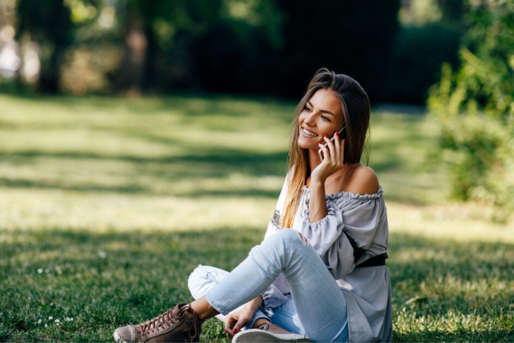 дівчина розмовляє по телефону в парку