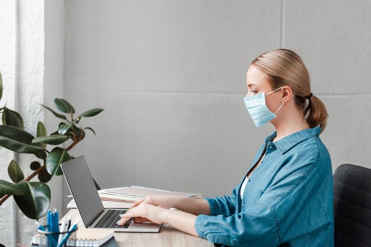 жінка в масці працює за комп'ютером