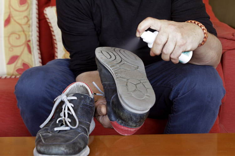 мужчина дезінфікує взуття