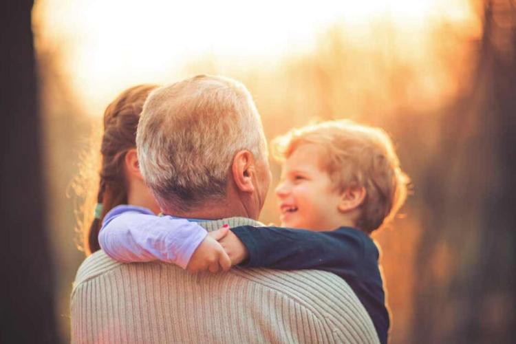 дідусь тримає онуків на руках