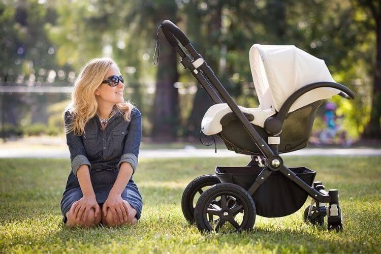 жінка сидить на траві біля дитячої коляски