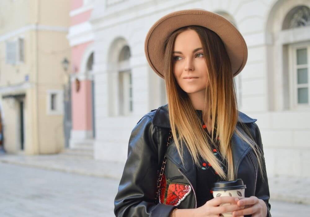 дівчина в капелюху тримає каву
