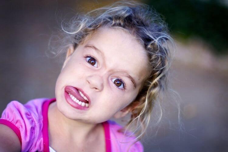 дівчинка показує язик